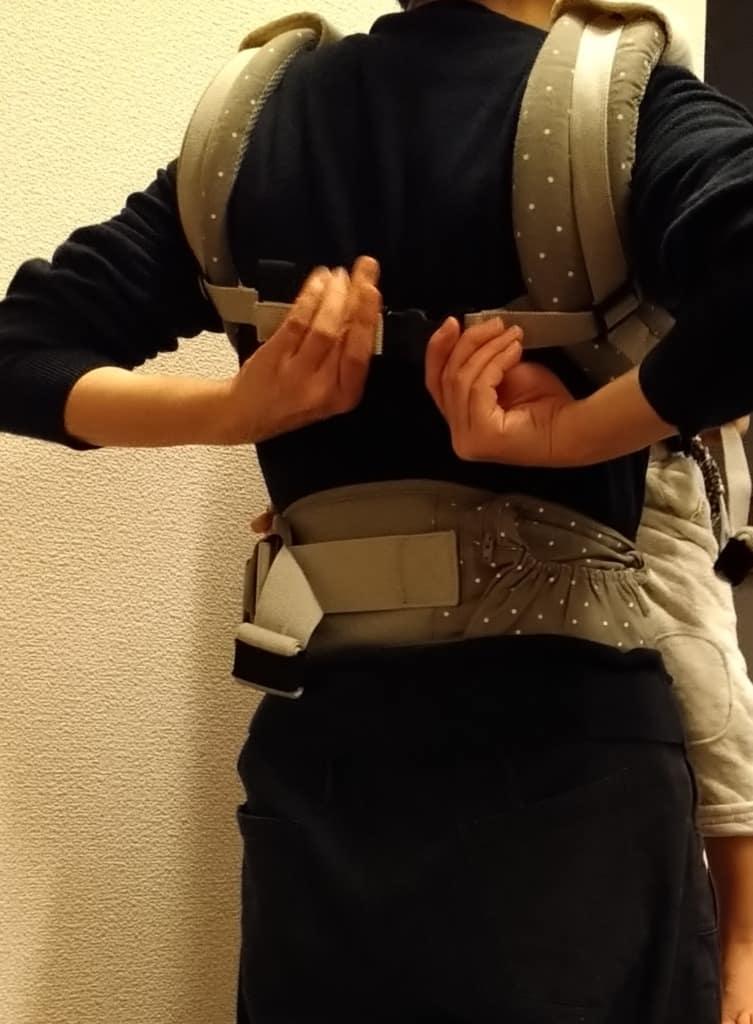 肩ベルトに腕を通し、バックルを留める